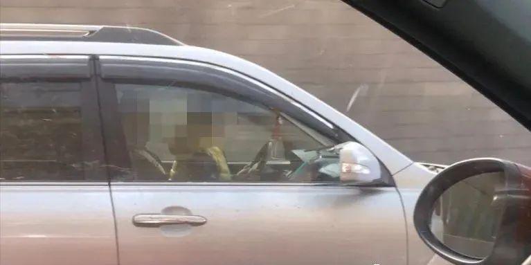 青岛胶宁高架上一驾驶员抱着孩子开车 孩子还扶着方向盘