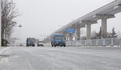 滨海大道附近道路难行 青岛市政人员冒雪保畅通