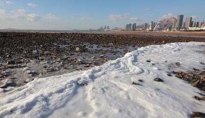 冻上了!青岛石老人海水浴场东侧沙滩现结冰现象