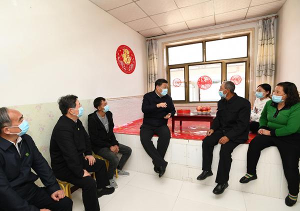 2020年5月11日,习近平在山西省大同市云州区西坪镇坊城新村,同搬迁户白高山一家人坐在炕沿儿上拉家常。